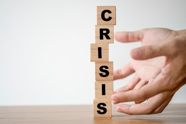 Mão proteger bloco de cubos de madeira que imprimir palavras de crise de tela. conceito de crise financeira e econômica. Foto Premium