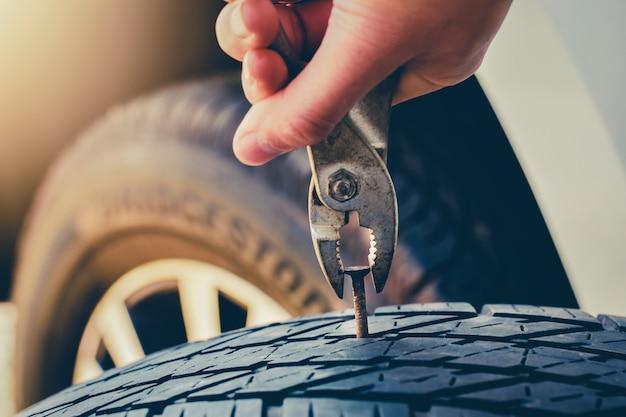 Mão puxando para remover um prego no pneu, pneu furado fixação e reparo o pneu está vazando do tack Foto Premium