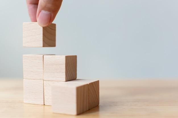 Mão que arranja o bloco de madeira que empilha como a escada da etapa na tabela de madeira. conceito de negócio para o processo de sucesso de crescimento. Foto Premium