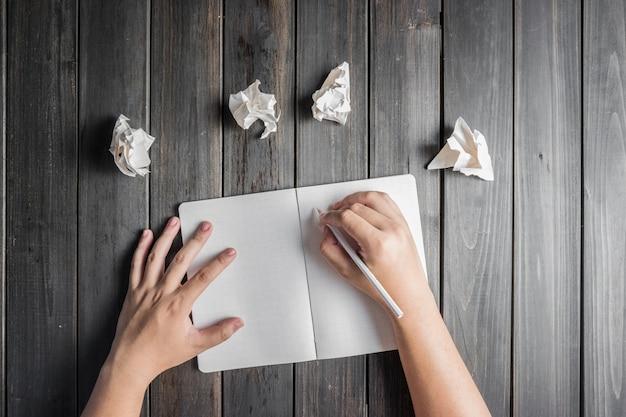 Mão que escreve ao lado de algumas bolas de papel Foto gratuita