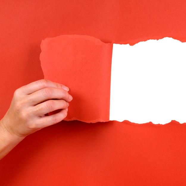 Mão que rasga um papel Foto gratuita