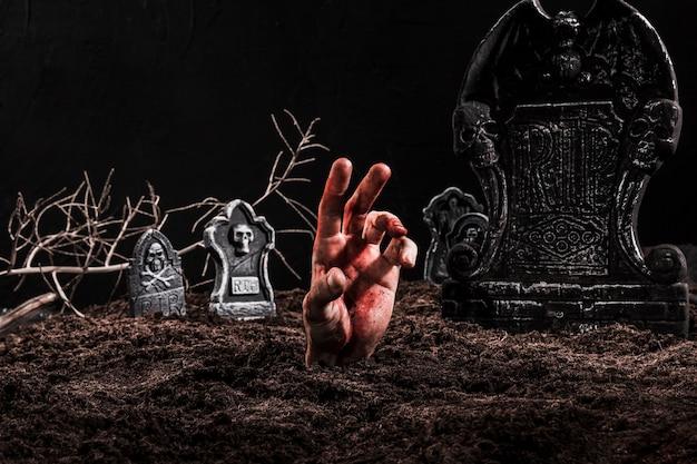 Mão saindo do túmulo no cemitério escuro Foto gratuita
