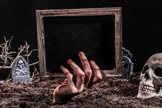 Mão, saliente, de, sepultura, segurando, quadro-negro Foto gratuita