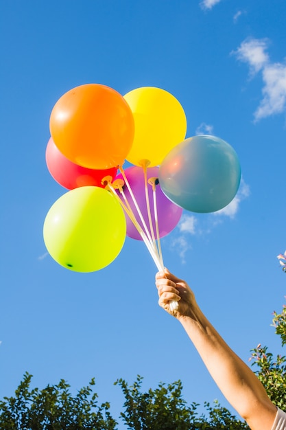 Mão segura, cobrança, de, balões brilhantes Foto gratuita