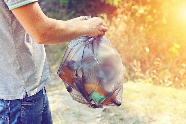 Mão segura, contra, floresta, lixo cheio, sacola plástica preta Foto Premium