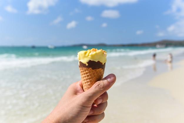 Mão segura sorvete no fundo da praia Foto Premium