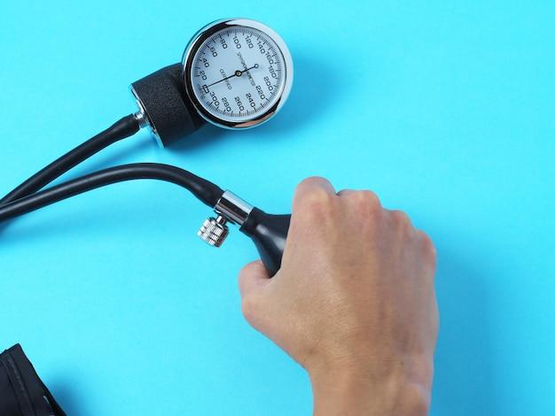 Mão segura um monitor de pressão arterial que mostra a pressão arterial Foto Premium