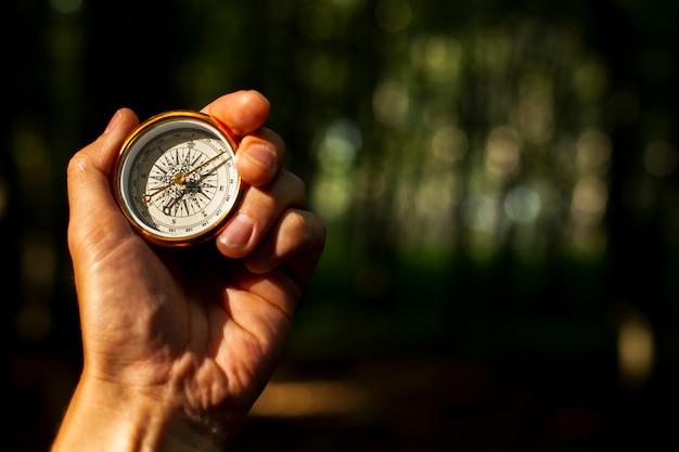 Mão segura uma bússola com fundo desfocado Foto gratuita