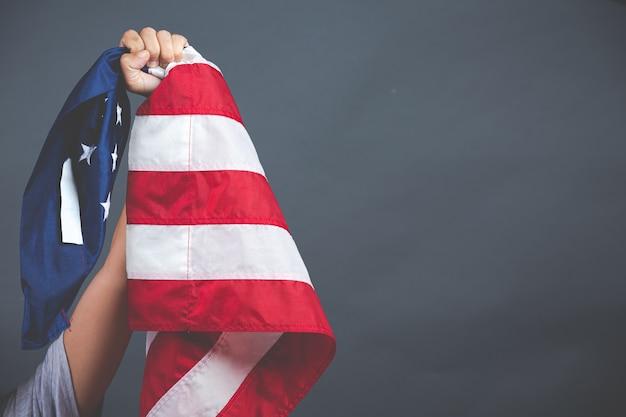 Mão segurando a bandeira dos eua em fundo escuro Foto gratuita