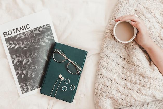 Mão segurando a bebida quente perto de óculos de livro e banner Foto gratuita