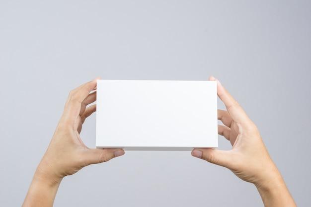Mão segurando a caixa branca em branco dar presente Foto Premium