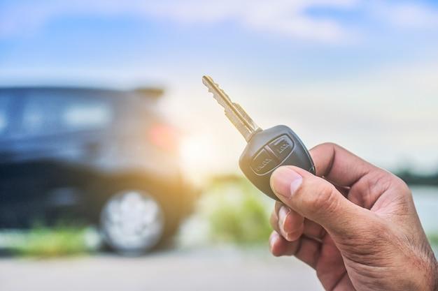 Mão segurando a chave e o carro estacionado na estrada Foto Premium