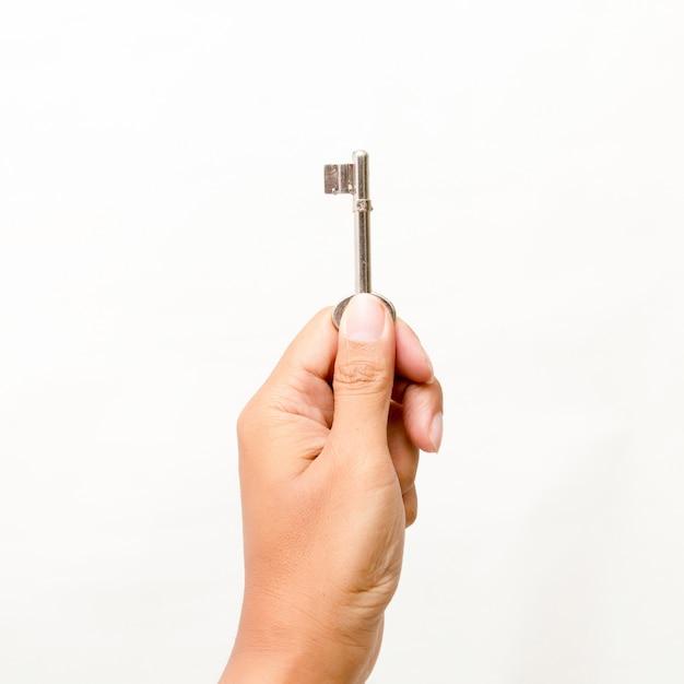 Mão segurando a chave isolado no branco Foto Premium
