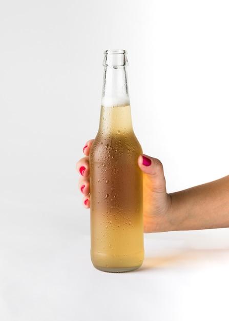 Mão segurando a garrafa de cerveja Foto gratuita