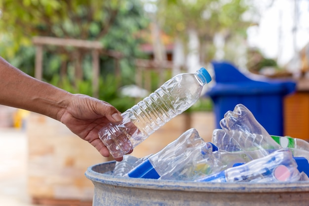Mão segurando a garrafa de plástico reciclável na lata de lixo para limpeza. Foto Premium