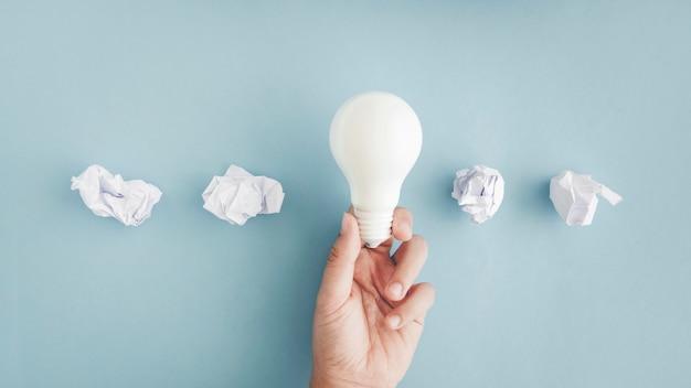 Mão segurando a lâmpada branca com bolas de papel amassado no fundo cinza Foto gratuita