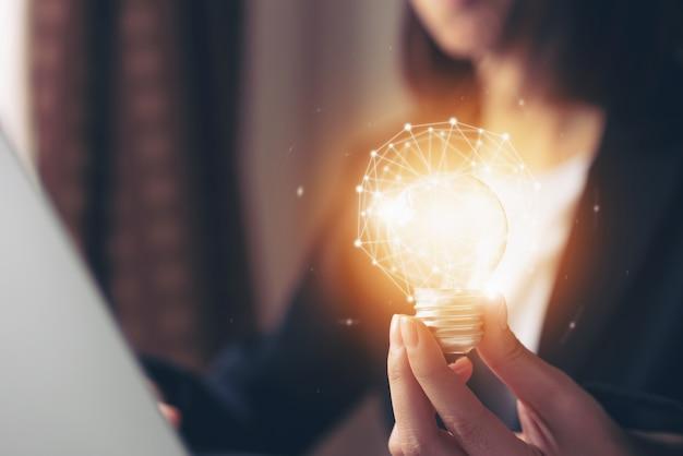 Mão segurando a lâmpada com inovação e criatividade são as chaves para o sucesso. Foto Premium