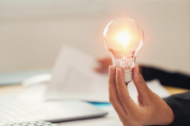 Mão segurando a lâmpada. conceito de ideia com inovação e inspiração Foto Premium