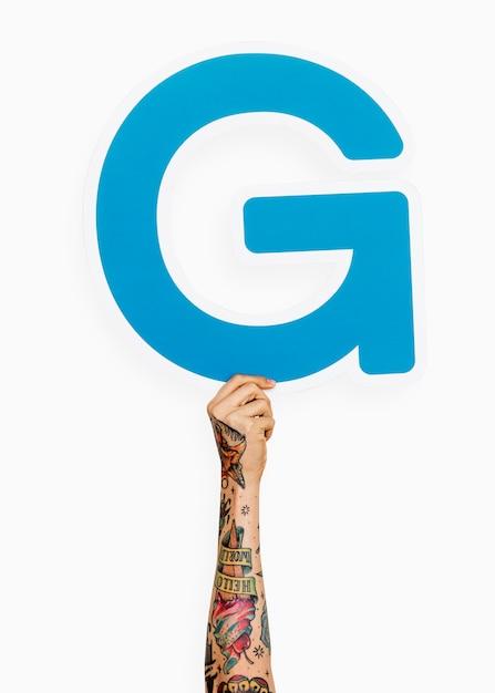 Mão segurando a letra g Foto gratuita