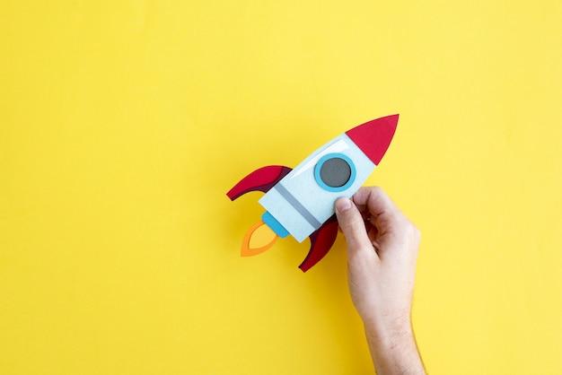 Mão segurando a nave espacial de foguete em fundo amarelo Foto Premium