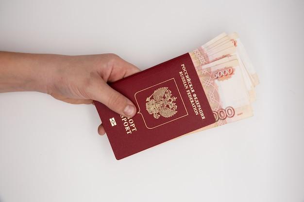Mão segurando a pilha de rublos russos pasport. Foto Premium