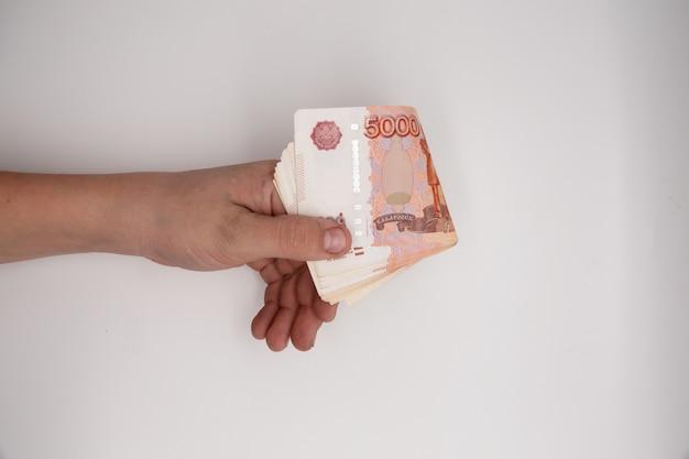 Mão segurando a pilha de rublos russos. Foto Premium