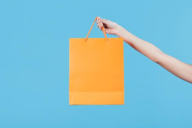 Mão segurando a sacola de compras no fundo liso Foto gratuita