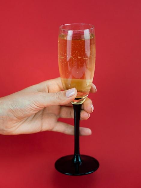 Mão segurando a taça de champanhe Foto gratuita