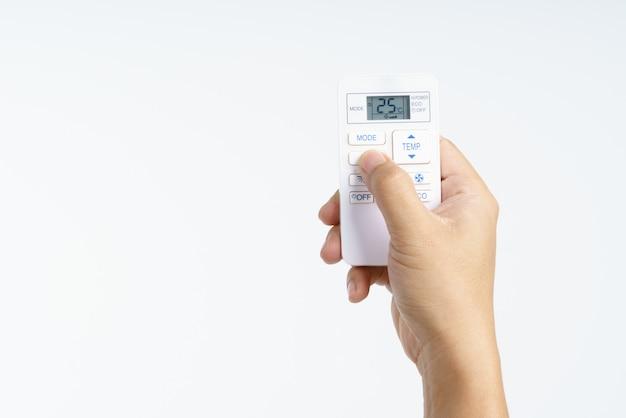 Mão segurando a temperatura de ajuste remoto do condicionador de ar a 25 graus celsius Foto Premium