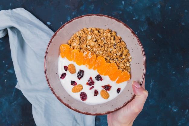 Mão segurando a tigela de frutas granola Foto gratuita