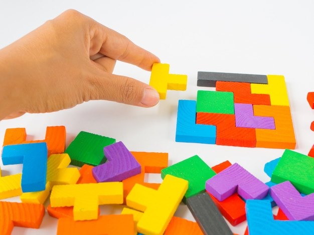 Mão segurando a última peça para completar um puzzle de madeira colorido quebra-cabeça tangram quadrado Foto Premium
