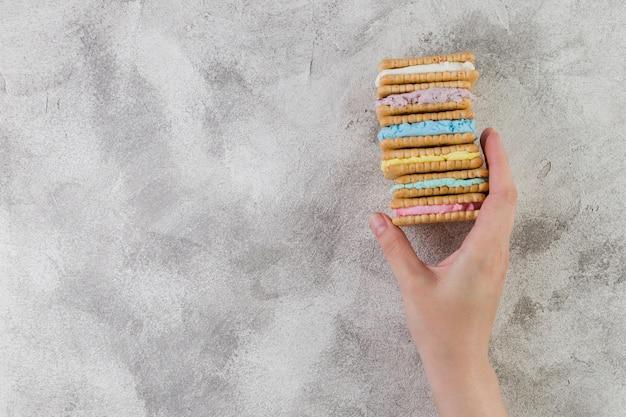 Mão segurando biscoitos saborosos no fundo cinzento Foto gratuita