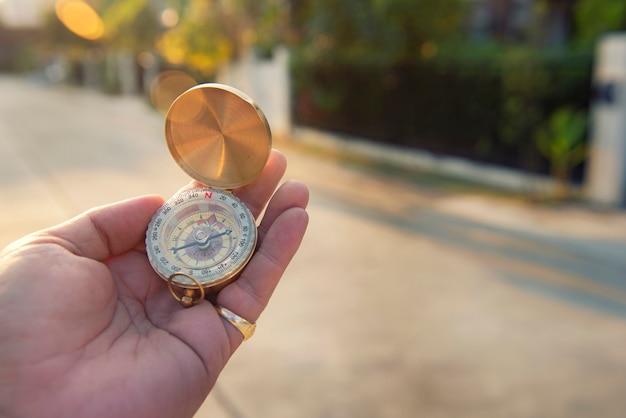 Mão segurando bússola à procura de direção. navegação, pesquisando Foto Premium