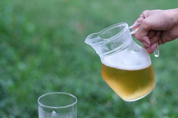 Mão segurando cerveja gelada para beber no tempo de relaxamento Foto Premium