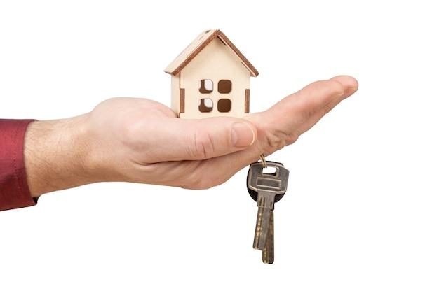 Mão segurando chaves e casa modelo. empréstimo hipotecário de aprovação de empréstimo e conceito de seguro Foto Premium