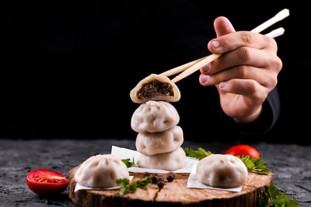 Mão, segurando, chopsticks, com, dumpling Foto gratuita