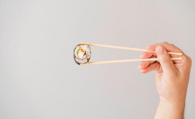 Mão, segurando, chopsticks, com, envoltório Foto gratuita