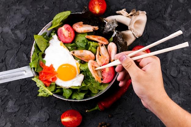 Mão, segurando, chopsticks, e, camarão Foto gratuita
