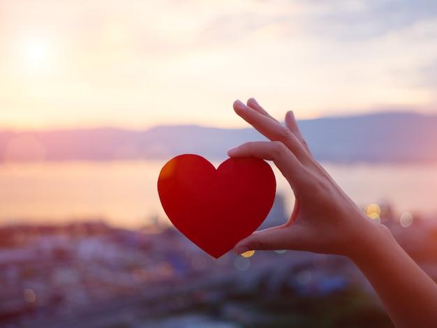 Mão segurando coração vermelho durante o fundo por do sol. Foto Premium