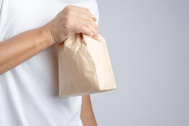 Foto Premium | Mão segurando crumble saco de papel marrom