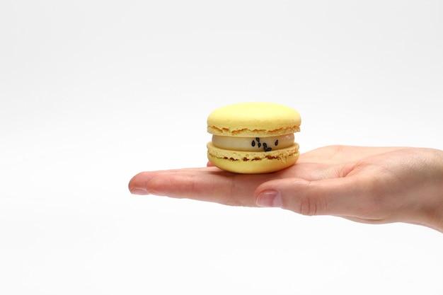 Mão segurando doce e colorido francês amarelo macaroons ou macaron isolado no fundo branco. Foto Premium