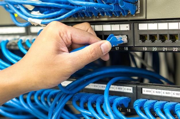 Mão segurando e conectando o cabo de rede conectar ao roteador e switch hub na sala do servidor Foto Premium