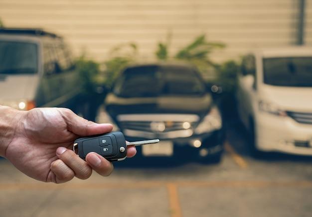 Mão segurando e tocar as teclas sobre a foto desfocada do carro usado para abrir o carro de porta Foto Premium