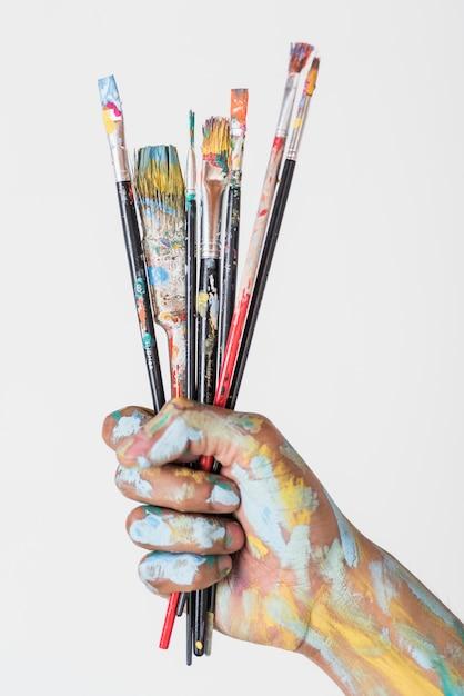 Mão segurando escovas manchadas com tinta Foto gratuita