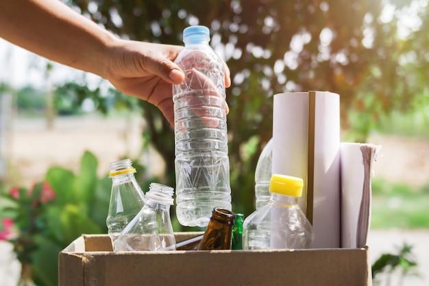 Mão, segurando, garrafa lixo, plástico, pôr, em, recicle sacola, para, limpeza Foto Premium