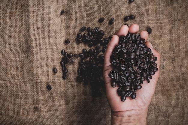 Mão segurando grãos de café Foto gratuita