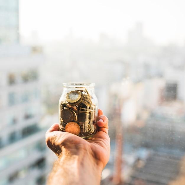 Mão segurando lata com moedas Foto gratuita
