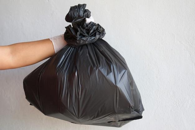 Mão segurando lixo saco preto isolado no fundo branco Foto Premium
