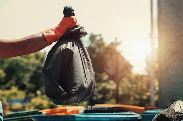 Mão, segurando, lixo, saco preto, pôr, para, lixo Foto Premium