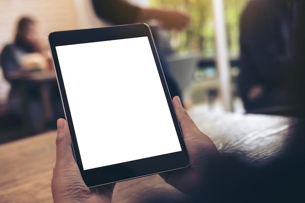 Mão segurando mock up tablet pc no café com as pessoas